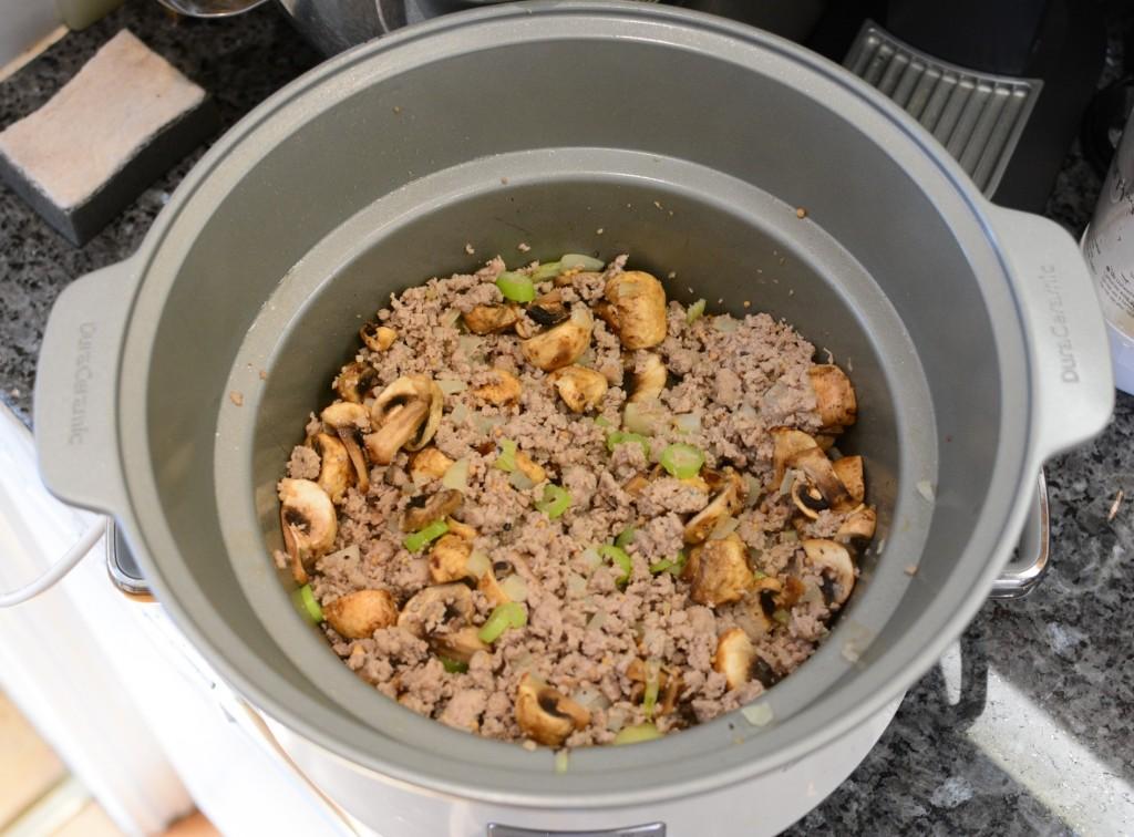 Korvfärs, lök och champinjoner har brynt i grytan på spisen.