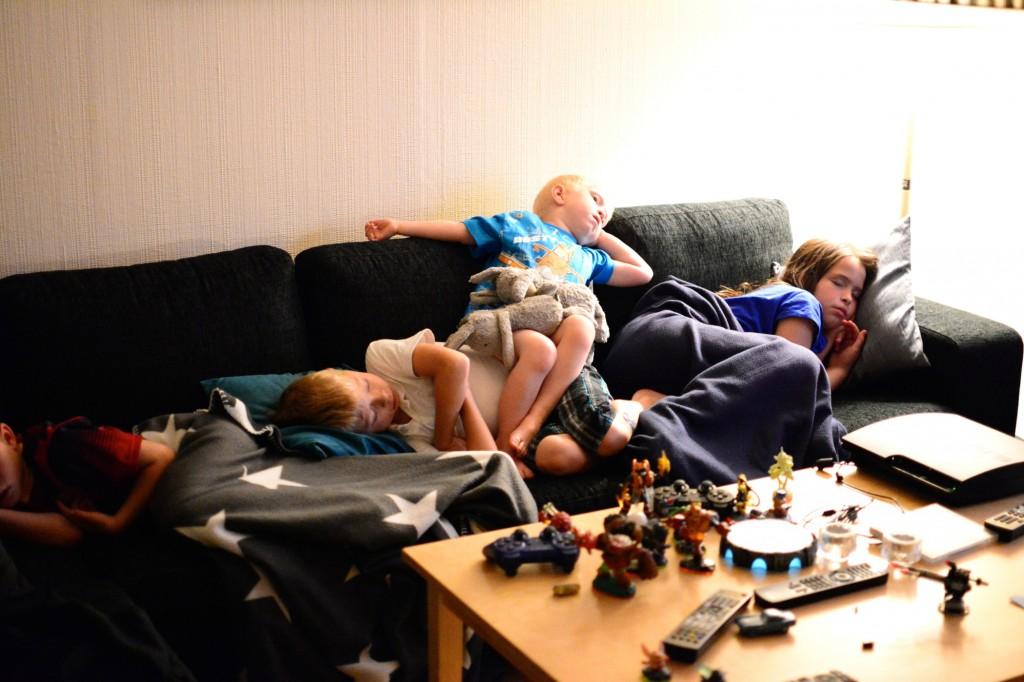 Trötta barn som slocknat i soffan