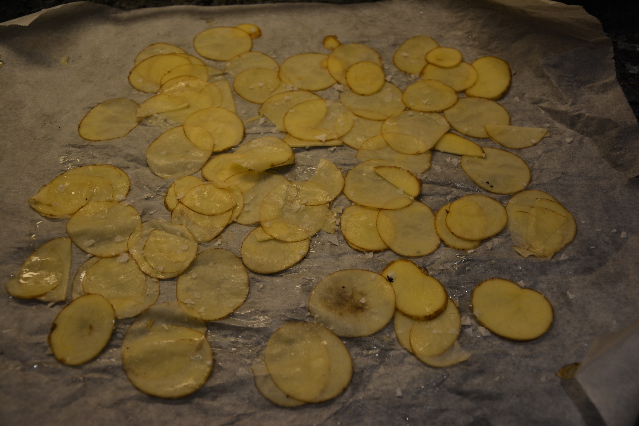 Lägg tunt hyvlad potatis på ett bakplåtspapper