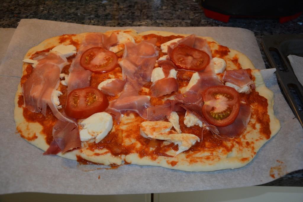 Ogräddad pizza med mozarella och parmaskinka.