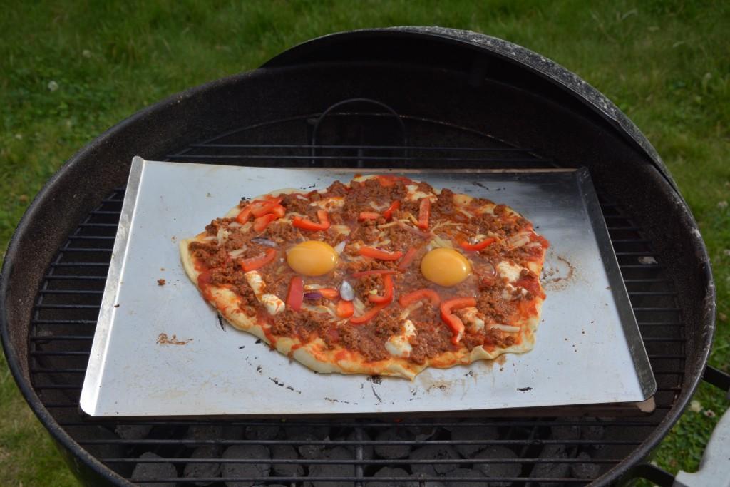 Köttfärspizza med ägg på grillen.