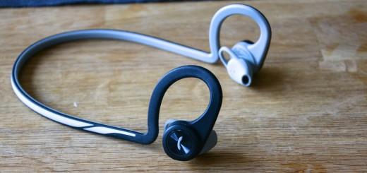 Trådlöst stereoheadset med byglar som träs runt öronen hopkopplat med ett halvstyvt nackband