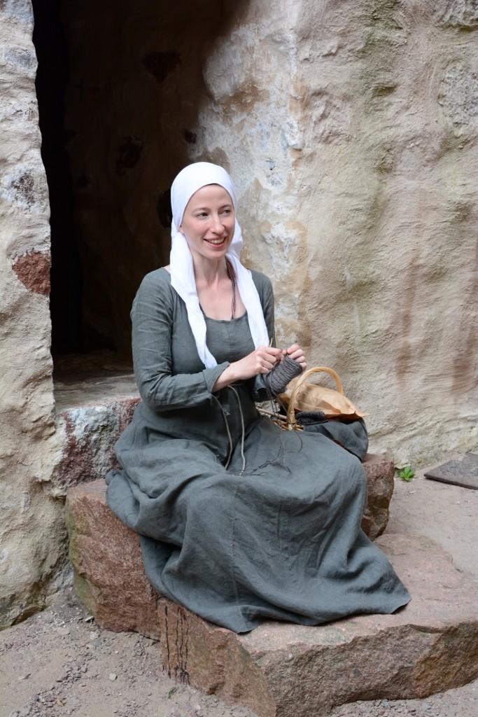 En av de anställda på museet i tidstypiska kläder och utövandes nålning.