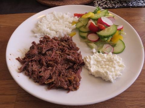 En första portion av pulled beef, ris, keso, såser och grönsaker