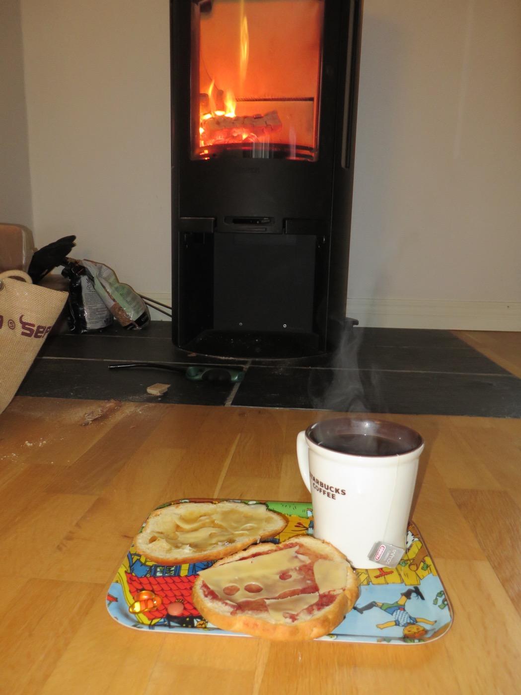 Nybakta scones och varmt te framför en tänd brasa