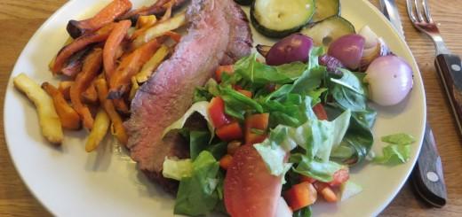 Grillad flankstek, sötpotatispommes, grillad lök och squash, grönsaker och såser.