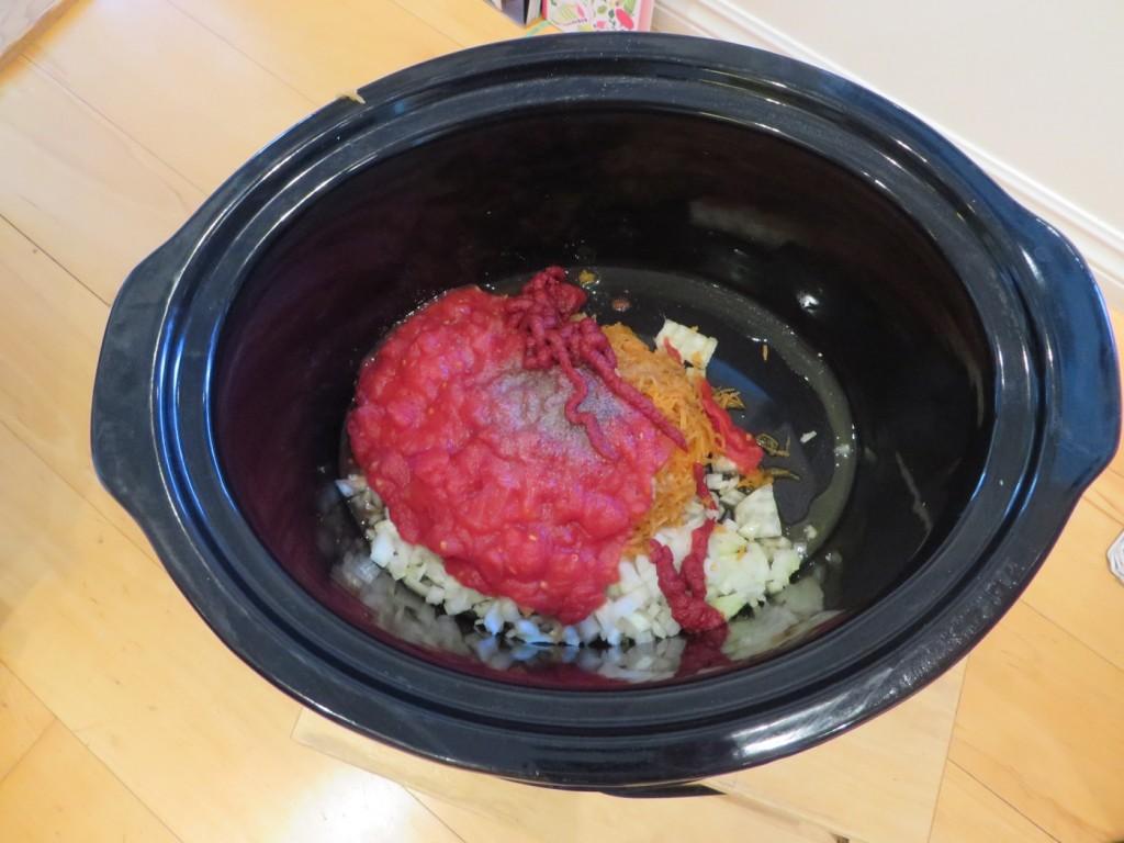I med lök, vitlök, tomatpuré, krossad tomat, rivna grönsaker, linser och kryddor.
