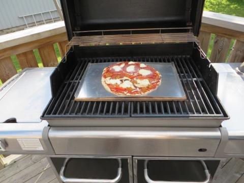 Pizza gräddas på bakstenen på grillen