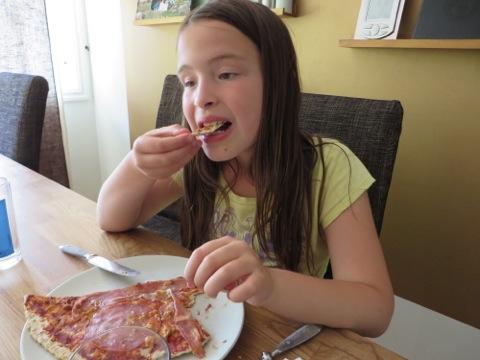 Filippa tar en tugga av sin pizza