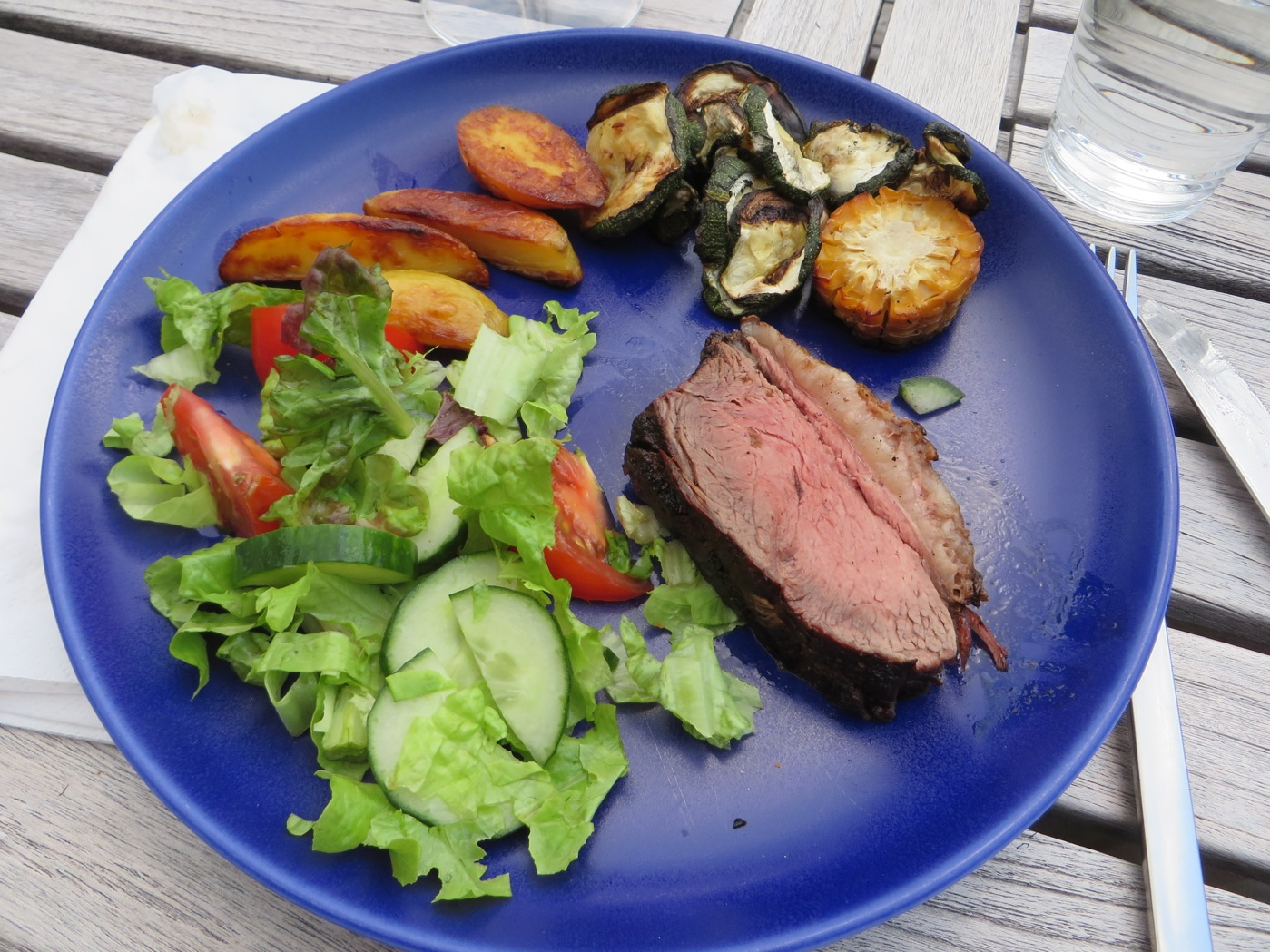 Kött, klyftpotatis, grönsaker, sallad och såser