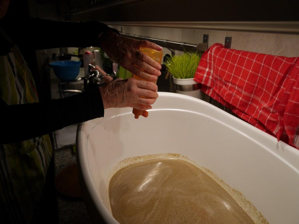 Svärmor blandar ihop alla ingredienser i en stor bakbalja.