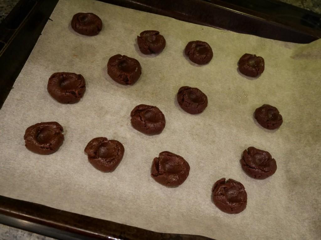 Nutellagrottorna läggs på bakplåtspapper och sedan skjuts in i ugnen.