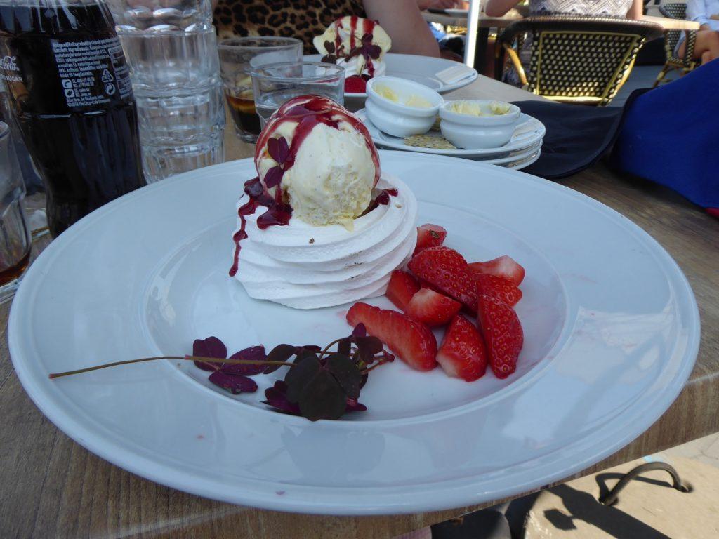 Jordgubbar serverade med vaniljglass, maräng och hallonsås