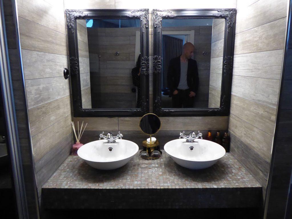 Stort badrum med två handfat, bubbelppol, två duschar och toalett.