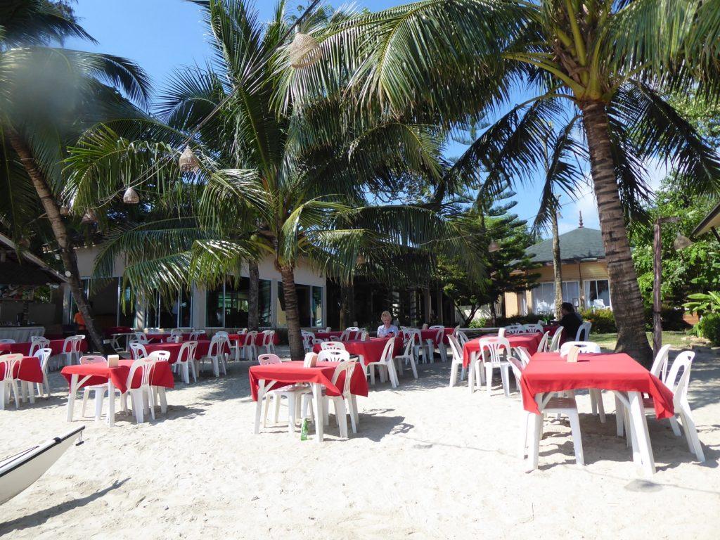 Hotellets restaurang med bord på stranden.