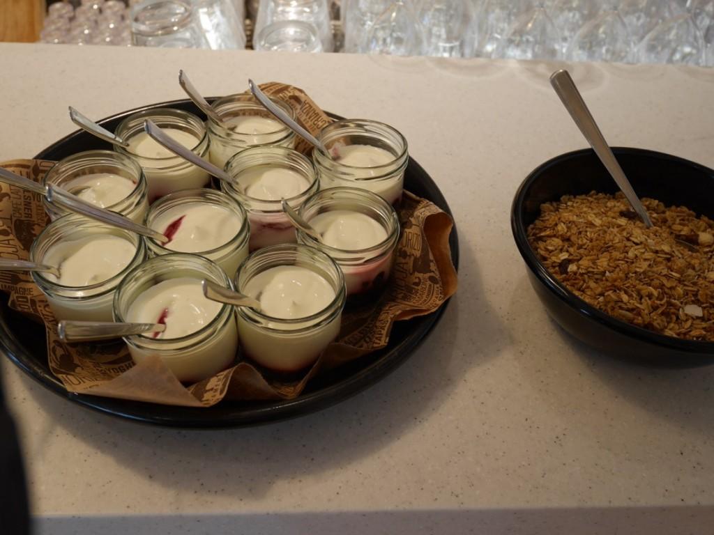 Syrlig turkisk yoghurt med bär i botten och granolatopping på sidan om.