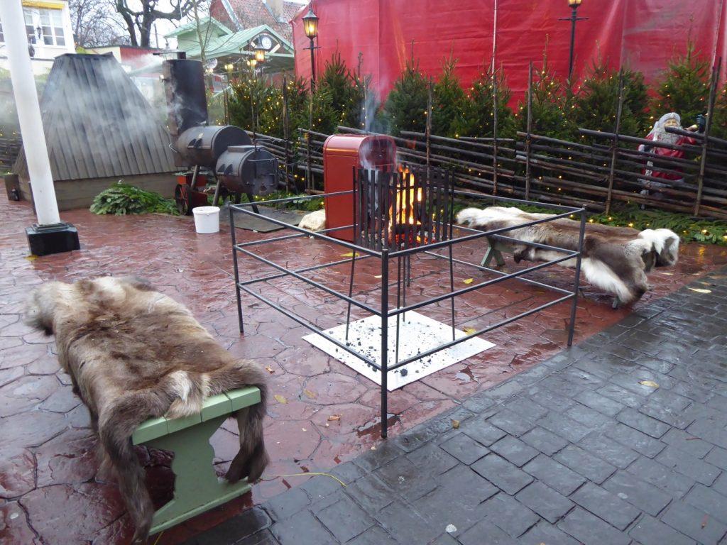Sätt dig på en av renhudarna, njut av glögg, julmusik och lukten från all mat som röks och grillas på gården.