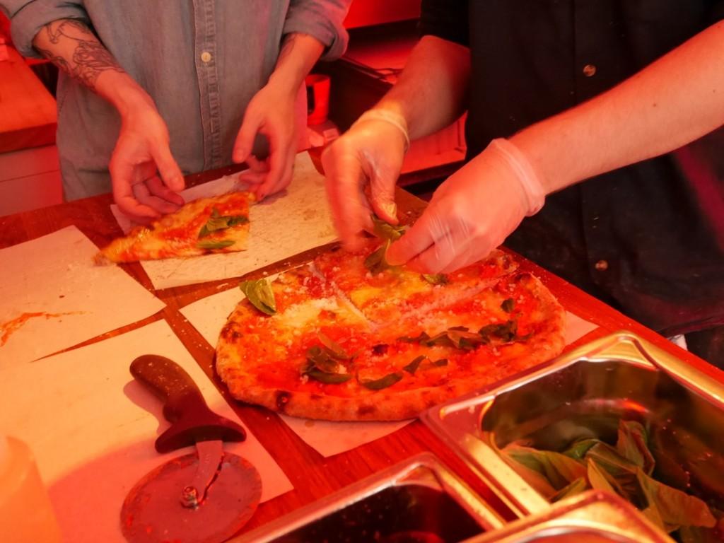 Sista handen läggs på pizzan.