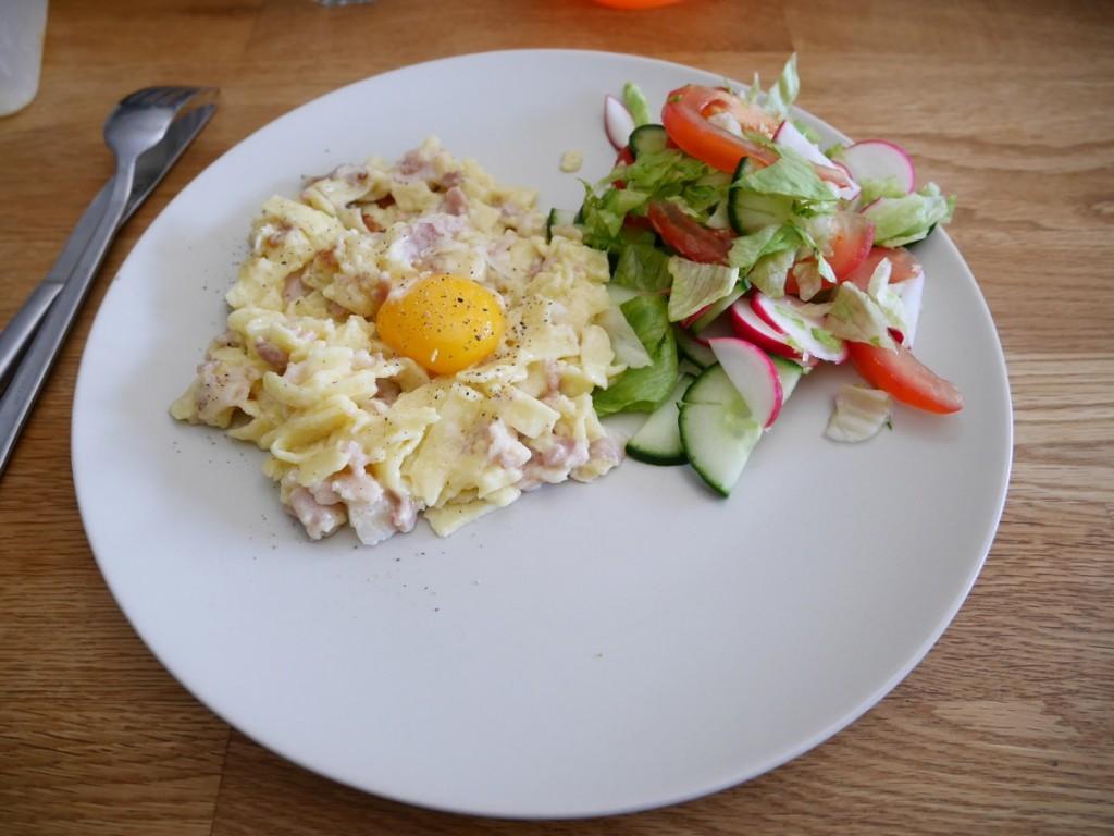 Servera Carbonara med äggula, extra parmesan och sallad.