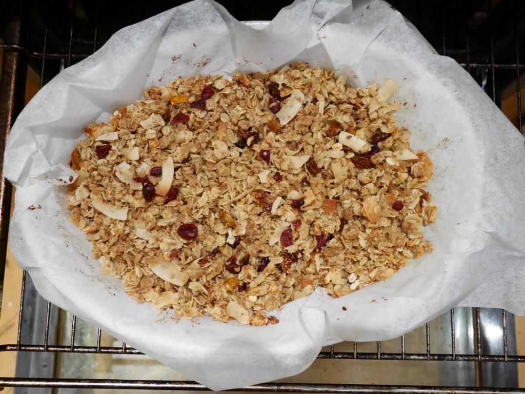 När granolan har rostats klart i ugn tillsätter man torkad frukt och kokoschips.