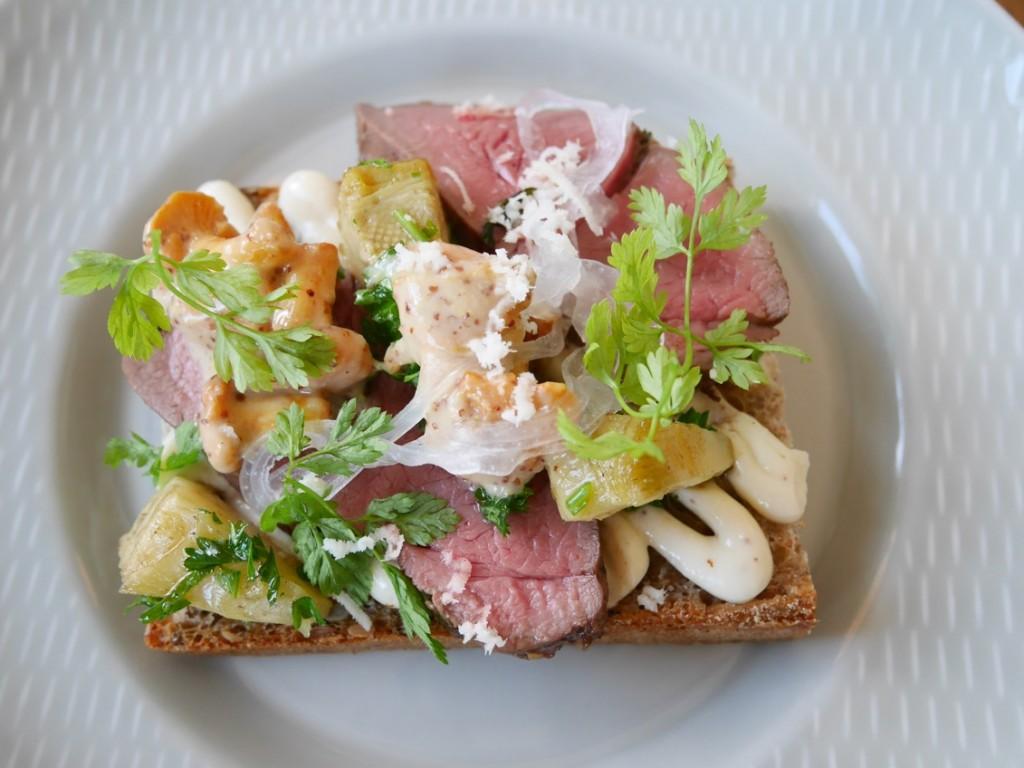 Tredje rätten ett smörrebröd med senapskräm, fina skivor rådjur, picklade kantareller och kronärtskocka.