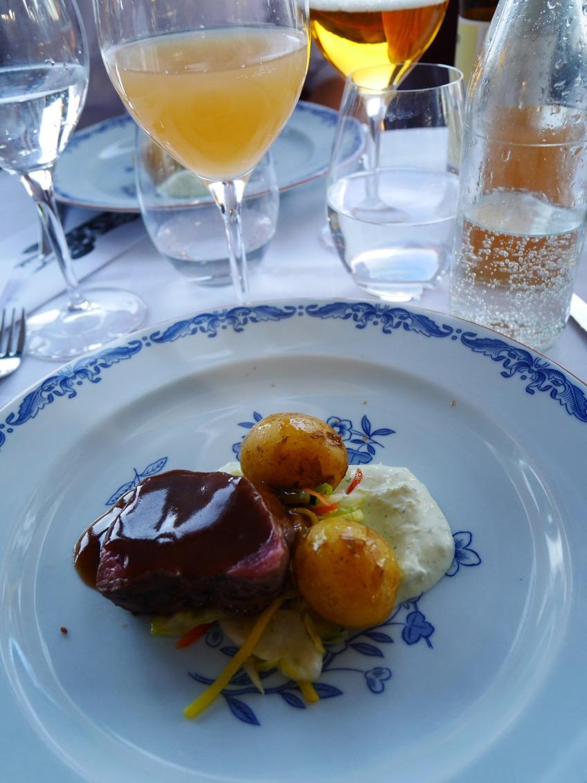 Hjortsadel med timjan, konfiterad färskpotatis med hyvlad ragu på primörer, örtcreme samt mustig rödvinssås med märg