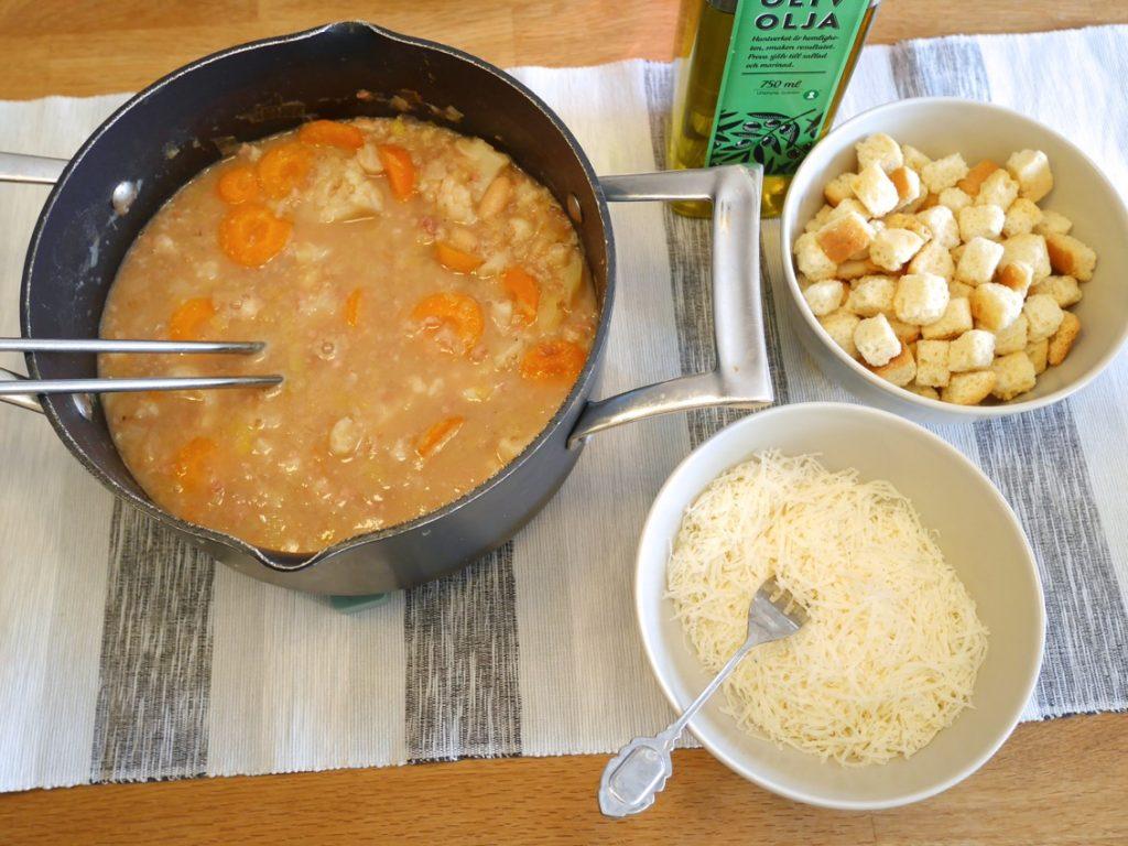 Servera soppan med parmesanost, krutonger och olivolja.